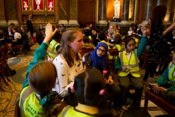Holly sits with a group of children in Drapers Hall