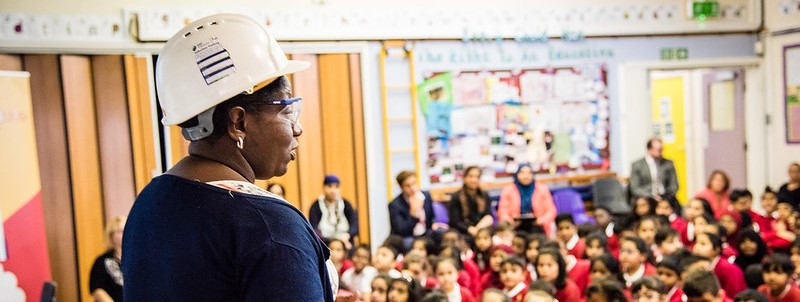 A woman wearing a hard hat and goggles talks at an assembly of primary children in a school hall.